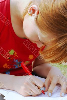 A girl`s writing on her knees