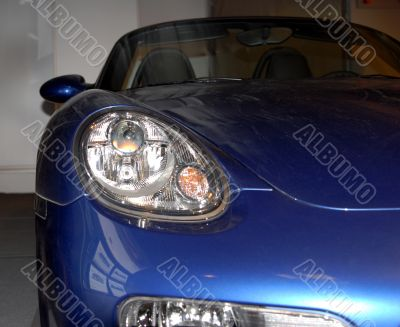 Headlight of the dark blue sports automobile.