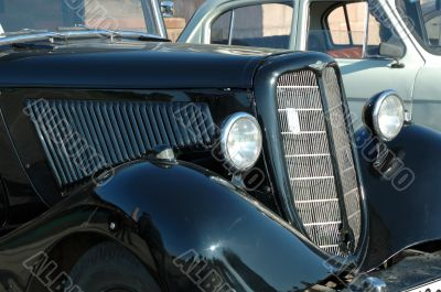 Forward part of the old automobile. A cowl and headlights.