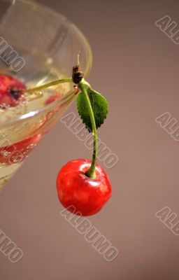 Red cherry on edge of a glass for a cocktail