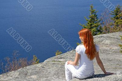 Girl sitting on a rock, enjoying the view