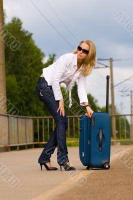 tired beautiful young lady with big suitcase