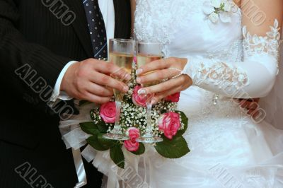hands of newlyweds with champagne cups
