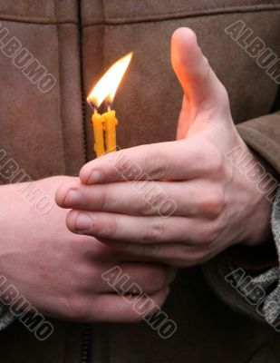 Flaming candle upon palms protection