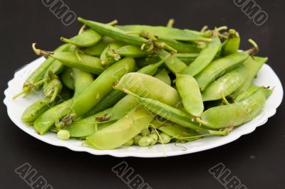 Peas pods on a white plate