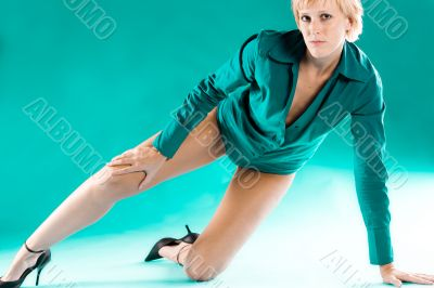Blond girl in green blouse stretching her leg