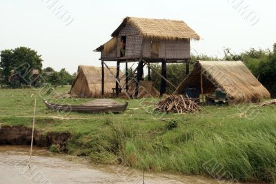 Hut and boat on the river bank