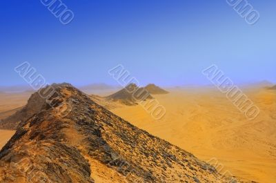 mountains and yellow sand in desert in mist
