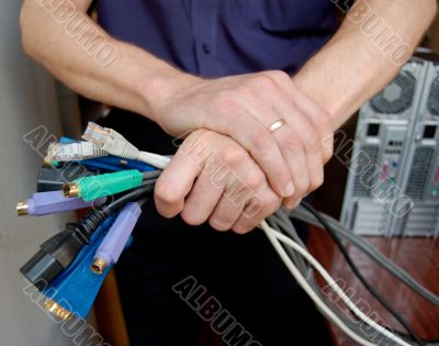 IT specialist holds on the cables in his hands