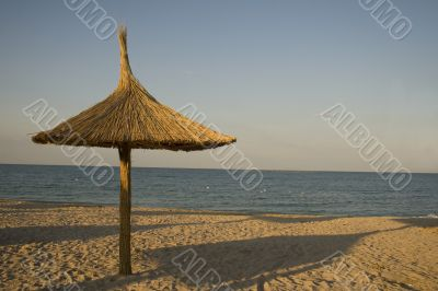 Single thatched umbrella on beach