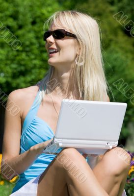 outdoor picture of lovely blonde with laptop