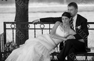 Newlywed couple relaxing on bench