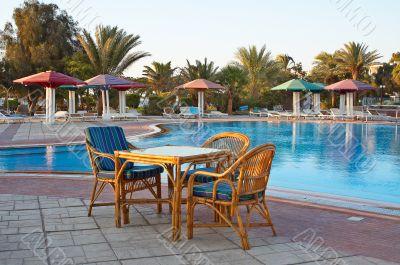 Three arm-chair near swimming pool.