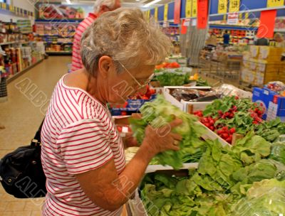 Old woman buys salad in a supermarket