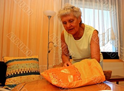 Old woman applies a seat cushion.