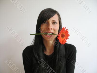 dark hair girl bitting a flower