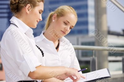 two happy businesswomen with paper chart