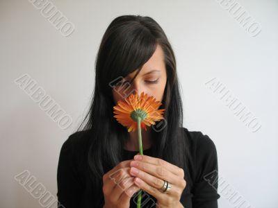 dark hair girl smelling a flower