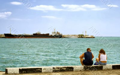 Summer day man and woman sitting at the berth