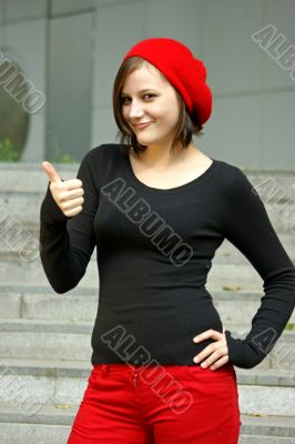 Girls with red cap stretches thumb in the air
