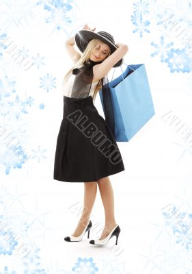blond in retro hat with blue shopping bag