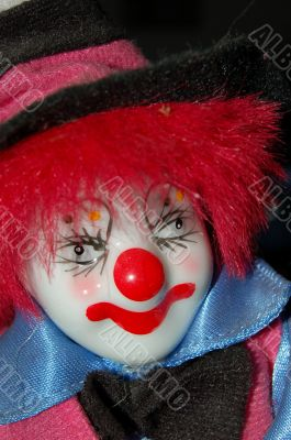 Head of toy clown wearing a black hat