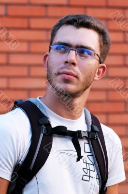 Man in glasses at the brick wall background