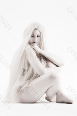 Long blond haired artistic beauty thinking