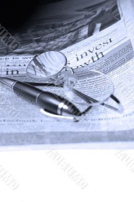 pen and glasses and newspaper