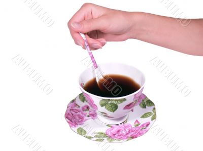 The female hand a spoon stirs tea