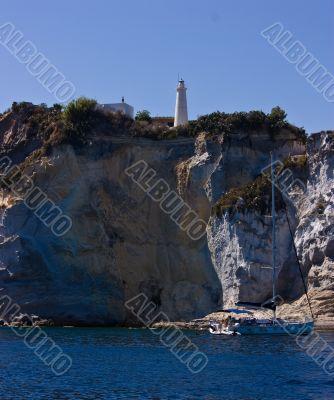 Lighthouse on steep mountain and sail yacht