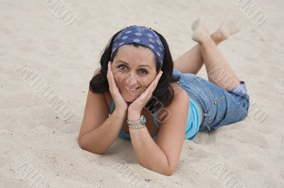 Adorable young woman lie down on the sand