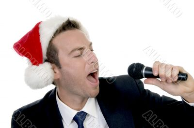 young man singing into microphone with santa cap
