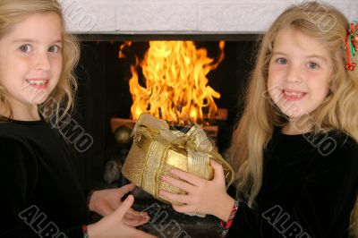 twin sister gift exchange by fireplace