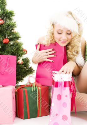 santa helper girl with gifts and christmas tree