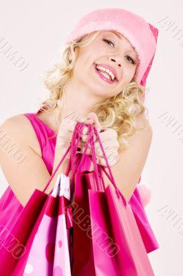 cheerful santa helper girl with shopping bags