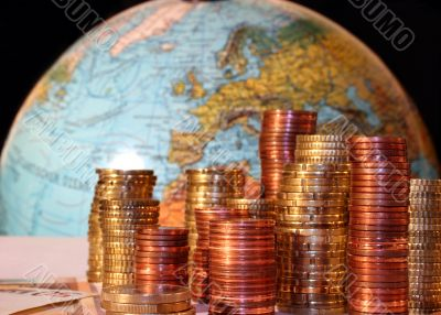 Stacks of Euro and Cent coins in front of a globe