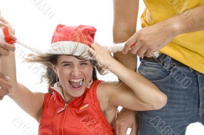 man pulling cap of woman