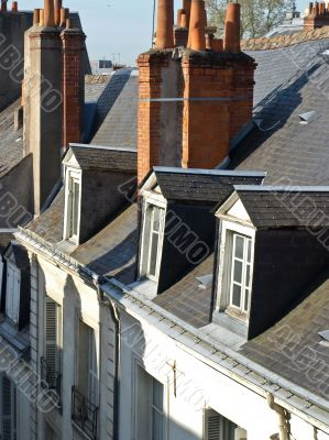 Roofs of a building with pipes and windows