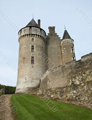 The medieval French castle standing on a grief, against the sky