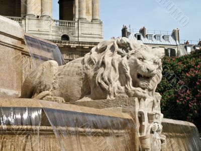 Sculpture of a lion on a fountain on the area in Paris