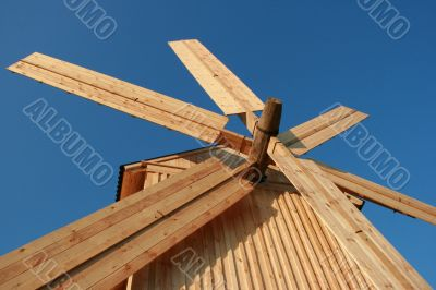 Rural wooden windmill against blue sky