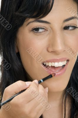 smiling lady putting lipstick