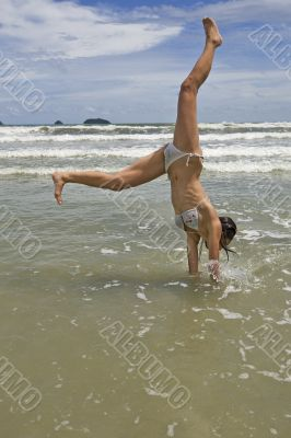 female teenager jumps on the beach