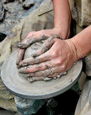 Hands shaping clay on potter`s wheel