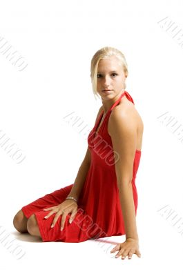beuatiful blonde teenage girl sitting on floor in red dress
