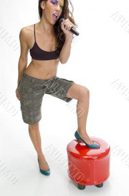 singer putting leg on stool