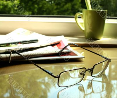 The eyeglasses, the newspaper  and the green cup