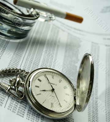 watch and  cigarette on documents