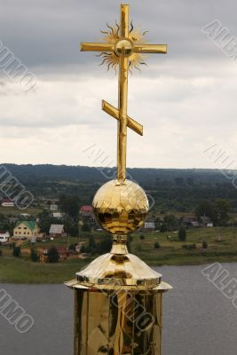 Gold cross with belltower`s reflection